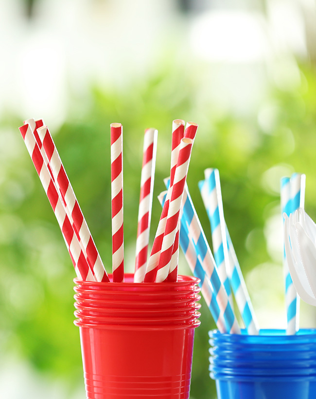 Straws and cups on a picnic table outside